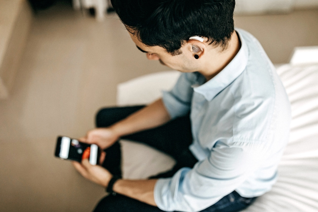 Young man looking at his phone with a hearing aid in his ear