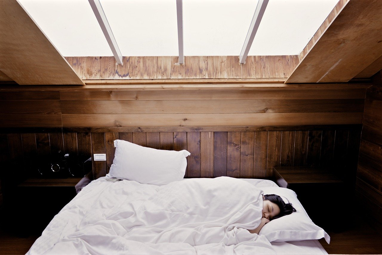 Woman in Bed, Room is Bright, Sleeping In Late Due to Insomnia