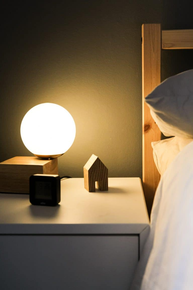 Photo of a nightstand next to a a bed.